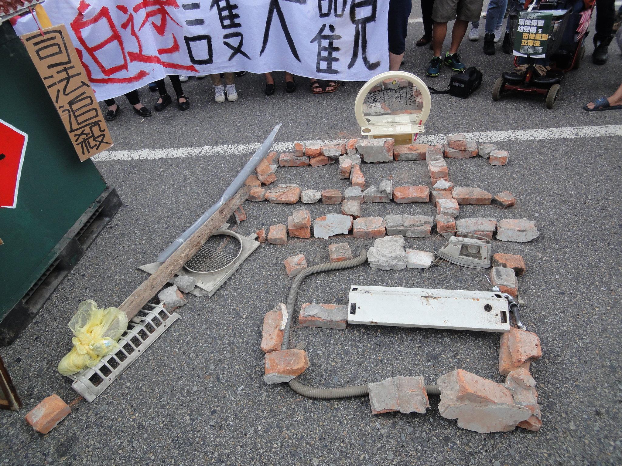 居民到達凱道後,將先前兩波強拆遺留下來的石塊、瓦礫排成「厝」字。(攝影:張智琦)