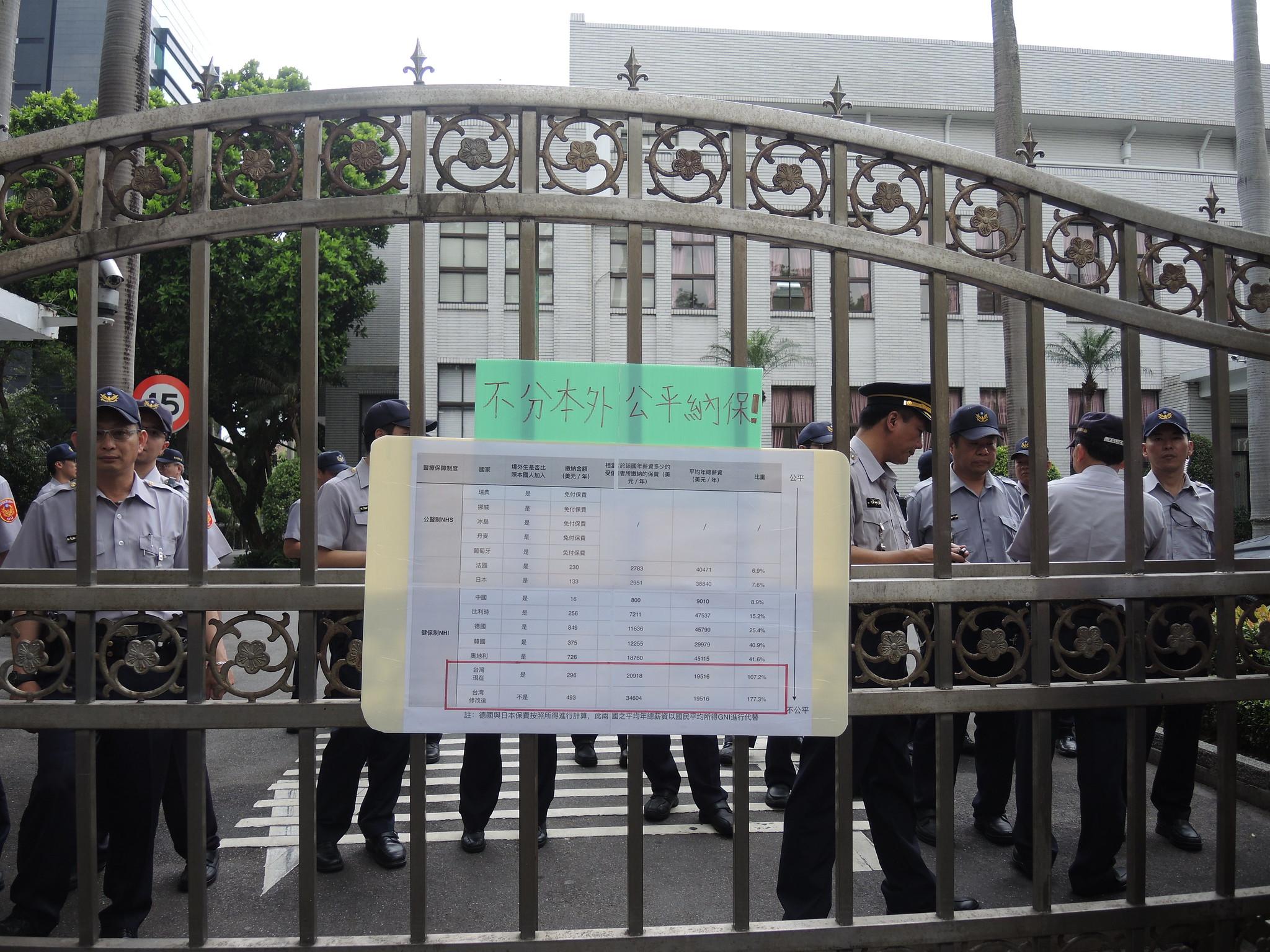抗議團體將各國比較健保費率的圖表貼在立法院大門,請立委參考各國標準制定法令。(攝影:曾福全)
