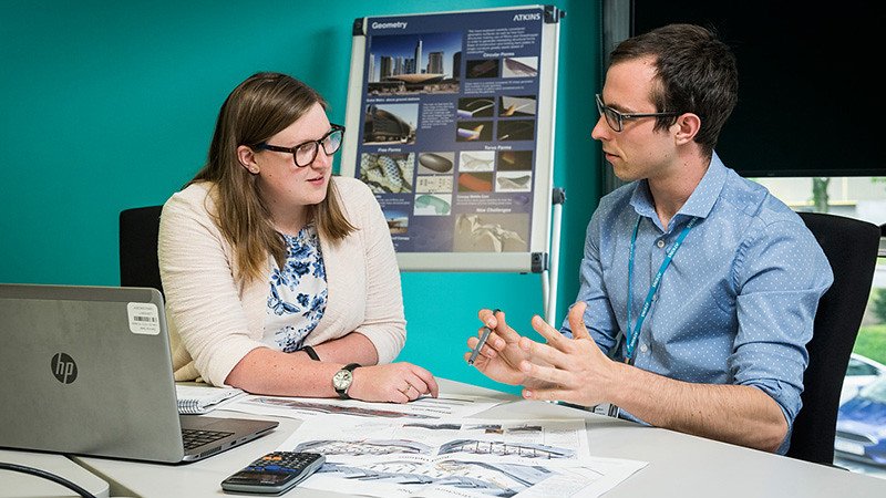Student talks over structural engineering plans at a table with his colleague