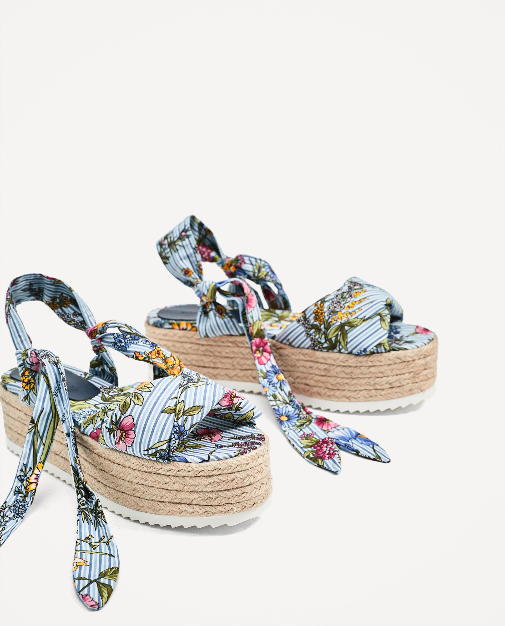 un paio di sandali con zeppa alta rafia e lacci con stampa floreale