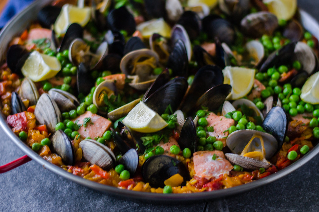 Seafood paella with chorizo is full of Pacific Northwest clams and mussels, wild salmon, spicy chorizo and garnished with sweet peas and bright lemon.