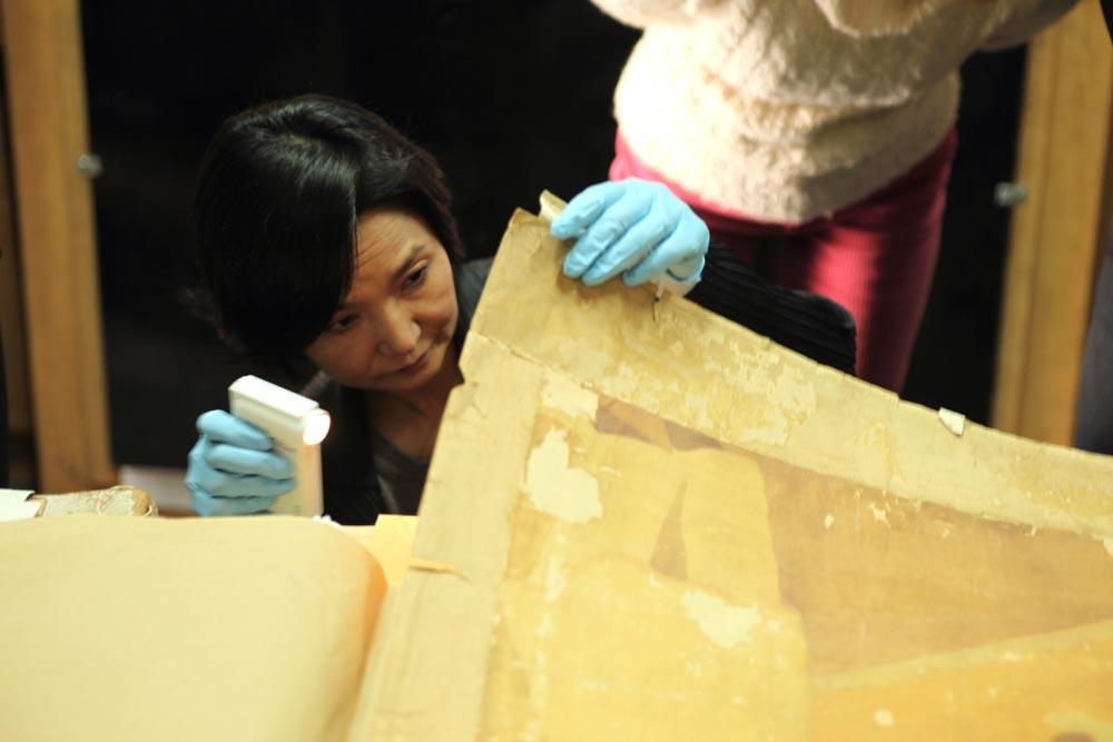ベトナム絹絵の状態を見る岩井さん(2011年、筆者撮影)