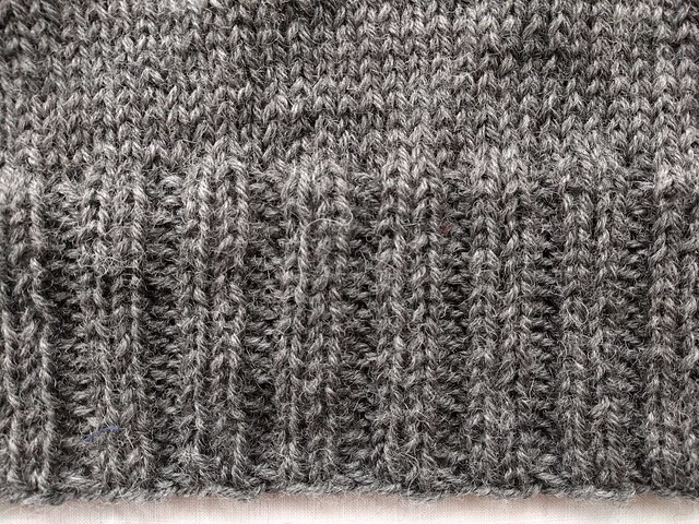 An image of grey hand knitted fabric. Top is stockinette, bottom is 2x2 ribbing.