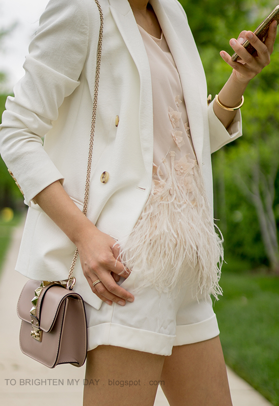 white blazer, nude top with feathers, white shorts, nude shoulder bag