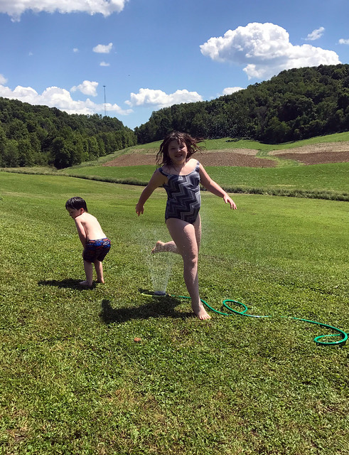 Lucy running through the sprinkler and what is Jack doing?