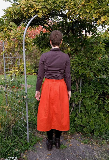Woman stands in garden archway. She wears a brown turtleneck long sleeve tee and an orange pleated skirt.