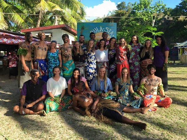 Auburn University students and members of the Mali tribe pose for a picture. They are all dressed in traditional Fijian attire.
