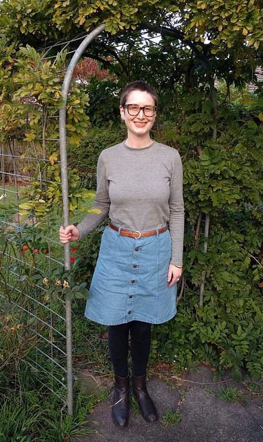 A woman stands in a garden under an arch. She wears a grey turtleneck skivvy, denim skirt and boots. She is smiling.