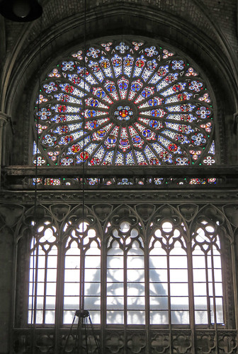 The stained-glass 'Rose' window in the Cathedral in Rouen, France framing a ghost of the outside ruin