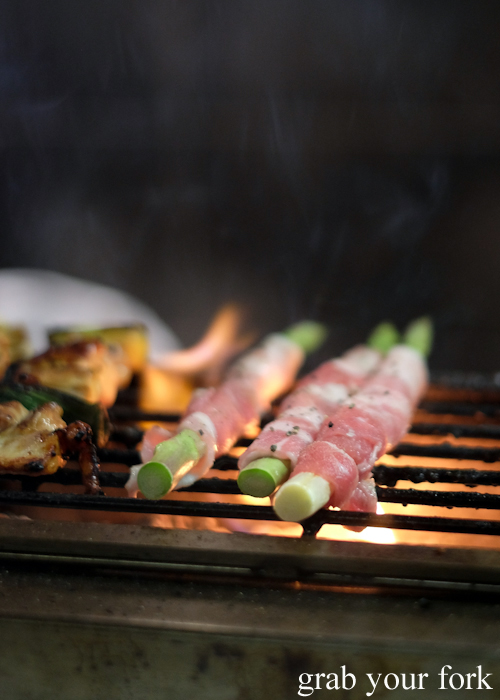 Charcoal barbecue asparagus wrapped in bacon at Yakitori Jin Japanese restaurant in Haberfield Sydney