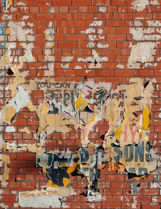peeling posters on brick wall in cardiff