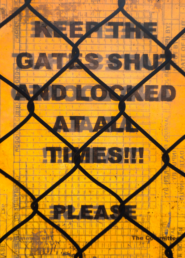 yellow poster behind fence