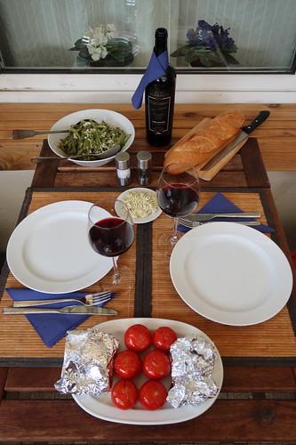 Gegrilltes Flanksteak mit Salbeibutter, Bohnensalat, heißer Tomate und Baguette (Tischbild mit ersten beiden Flanksteakstücken in Alufolie nachziehend)