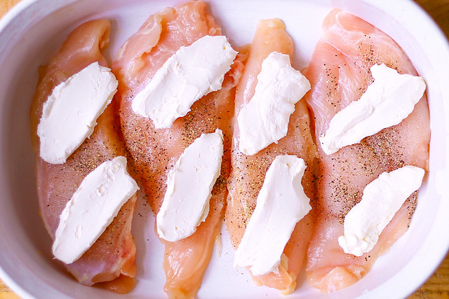 butterflied chicken breasts with cream cheese in white casserole dish
