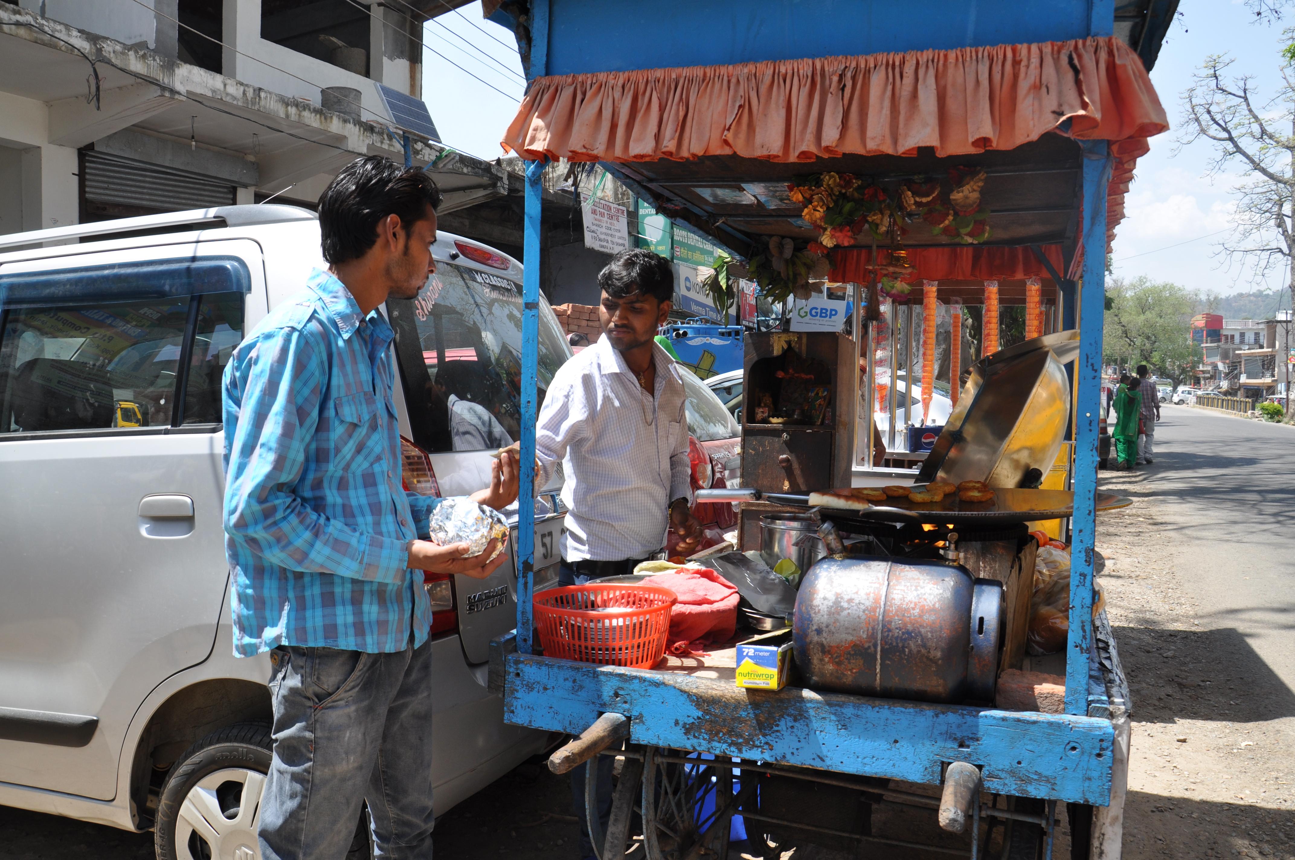 रवि ग्राहक को बर्गर देते हुए