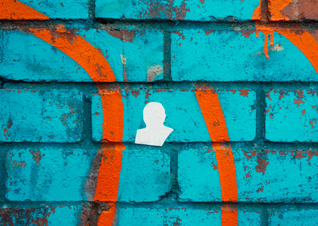 white silhouette sticker on blue and orange wall