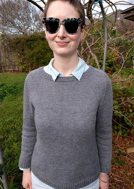 Woman stands in garden. She wears a handknit grey jumper over a denim shirt.