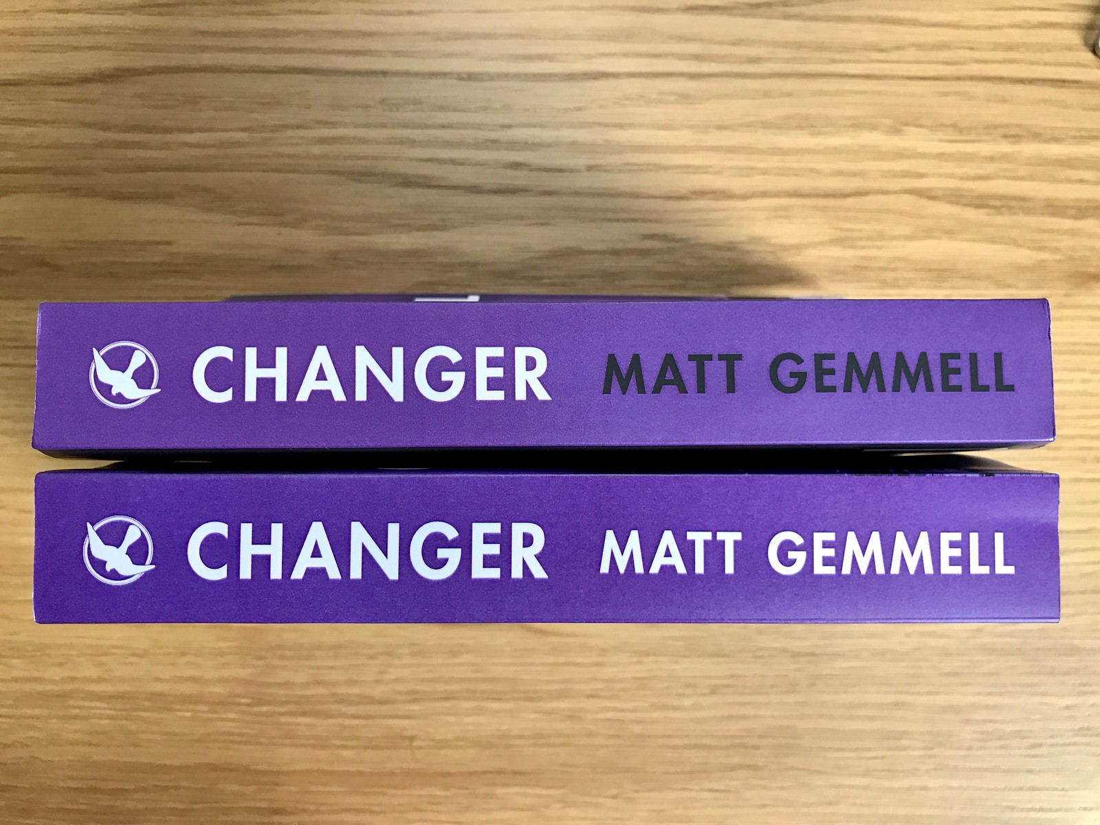 CHANGER new edition spine comparison, with the newer spine having the author's name in white instead of black.
