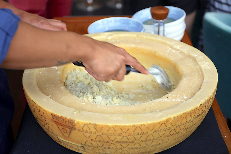 The risotto is cooked in a cheese wheel tableside