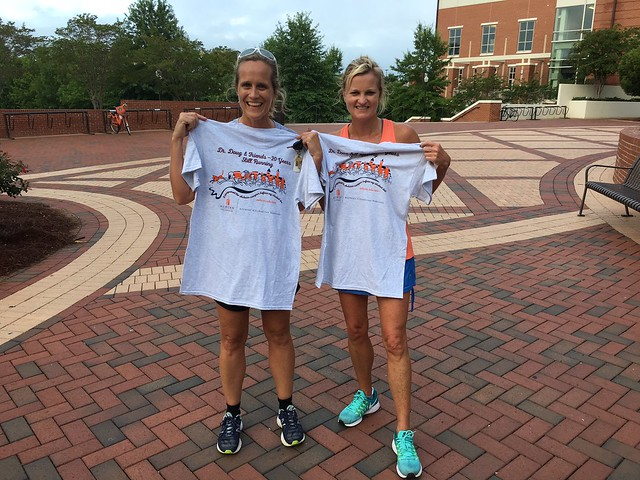 Two women pose for a picture while holding up Camp War Eagle Run t-shirts.