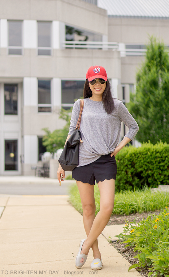 red baseball cap, gray twisted front top, black scalloped shorts, black tote, gray espadrilles