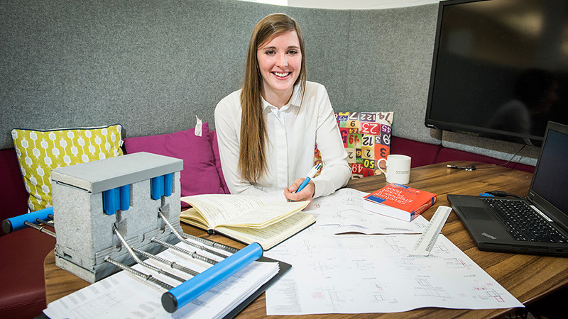 Student works at a desk surrounded by calculations in an office on placement