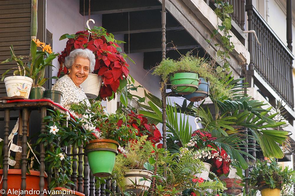 Vecina en el balcón de su casa regando las flores, en el viejo San Juan
