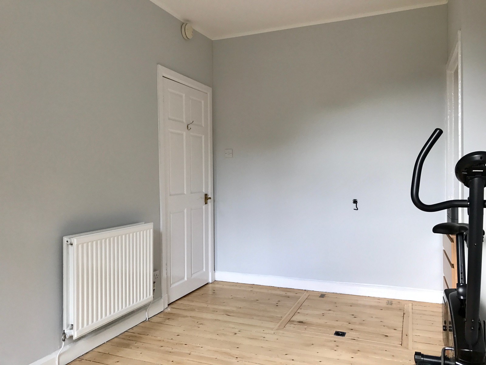 Photo taken from the opposite angle, as if sitting in my desk chair looking back towards the door in the diagonally opposite corner. All walls are soft grey, with white ceiling and woodwork, all completely blank. It's a contemplative, calming space.