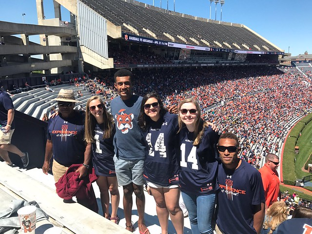 Three Fijian men stand in the stands of Jordan-Hare Stadium with three female students, all dressed in Auburn apparel.