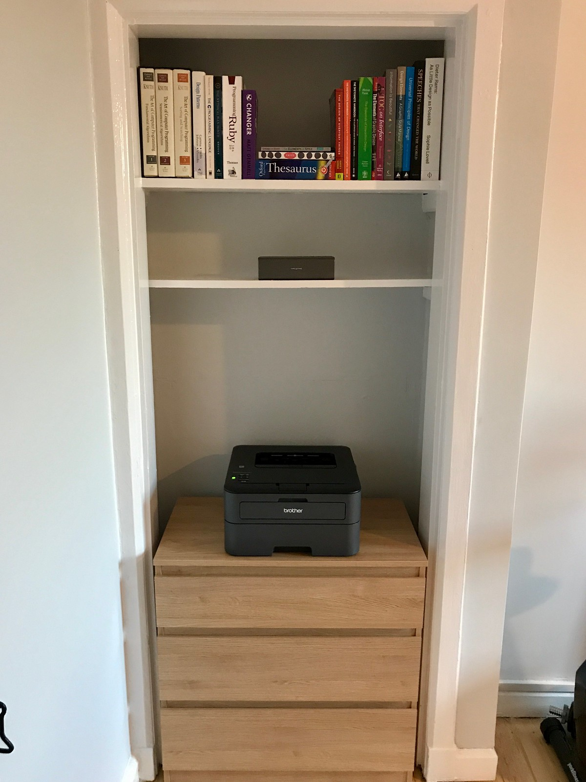 Photo of the printer and stationery-cupboard area directly opposite the door. It's a recessed area in the wall, within a shallow doorway, called an Edinburgh Press. Within it, there's a chest of drawers in oak veneer, 70cm high, holding a laser printer with three drawers below. Above, there are two shelves. The topmost has books, and the second has a Bluetooth speaker brick. No wires are visible anywhere.