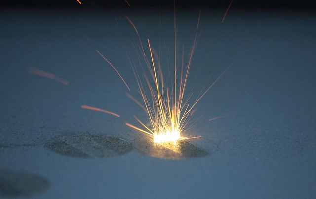 Metallic powder being heated during the additive manufacturing process.