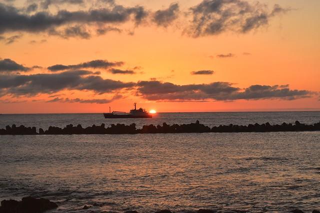 八丈島 海から昇る朝日と停泊する船