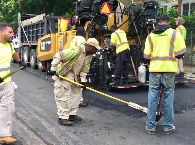 Huge pneumatic paver lays asphalt street