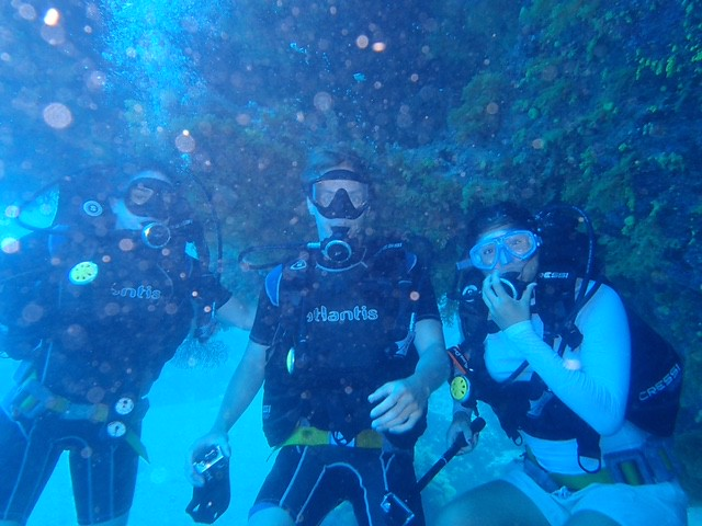 Three Auburn students pose for a picture underwater, among the Great Sea Reef.