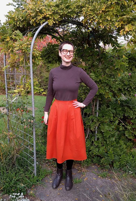 An image of a woman in a garden, standing under an arch. She wears a brown turtleneck long sleeve tee and an orange pleated skirt. Her hand is on her left hip and she is smiling.