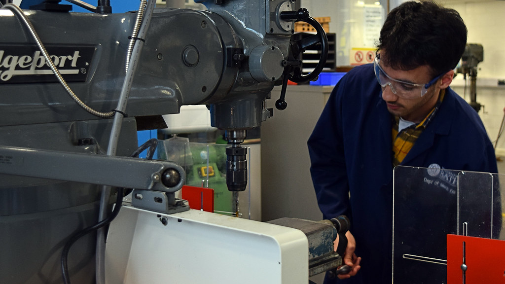 Student in lab coat and goggles works on CNC milling machine in workshop