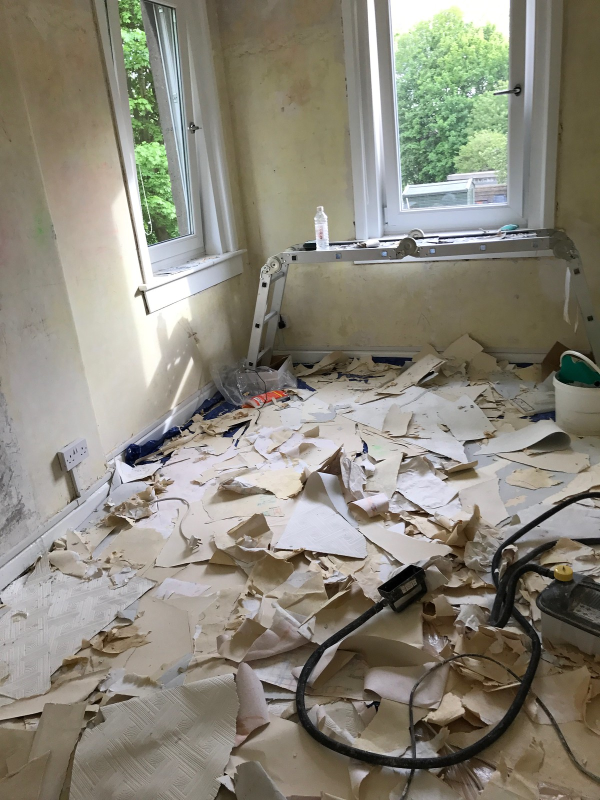 The room in a state of chaos, with stripped wallpaper littering the floor, and decorating equipment amongst the mess.