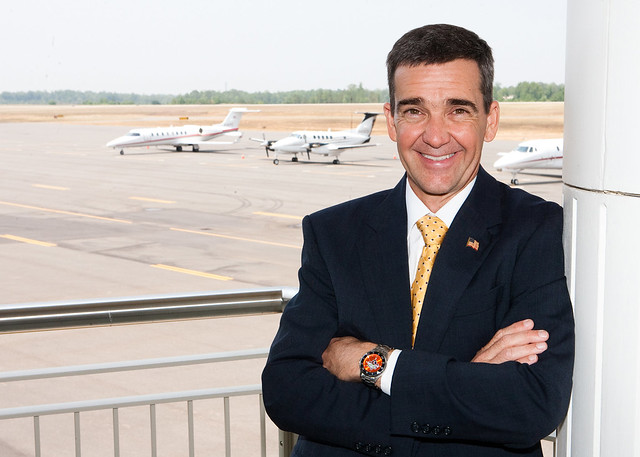 Bill Hutto stands on a balcony overlooking airplanes at the Auburn University Regional Airport.
