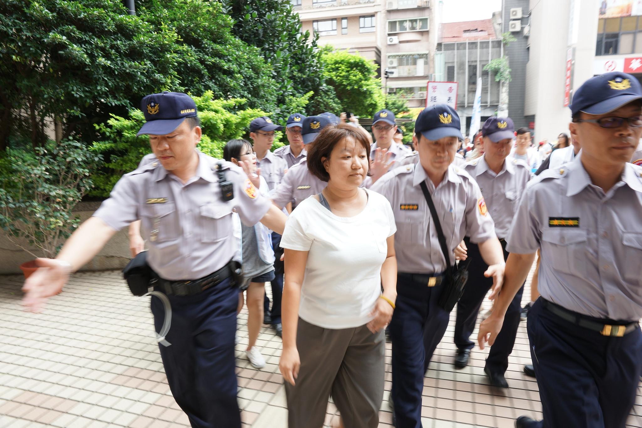李怡萱在警方护送下离去。(摄影:王颢中)