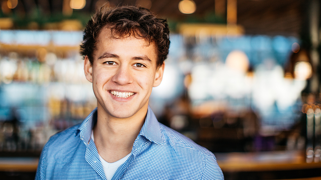 A young man in a blue shirt smiling at the camera