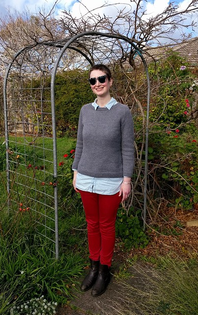 Woman stands in garden archway. She wears a grey handknit jumper, denim shirt, red jeans and ankle boots.