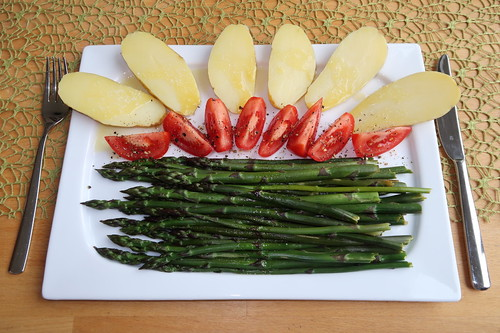 Violetter Spargel mit zerlassener Butter, halben Kartoffeln und Tomaten