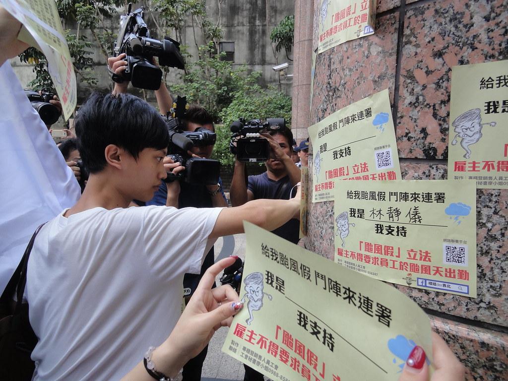 抗議勞工將連署支持颱風假立法的傳單貼在勞動部的柱子,目前網上已有超過600人連署。(攝影:張智琦)