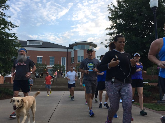 A group of parents are joined by Moose the dog as they run on Auburn's campus for the Camp War Eagle Parent Run.