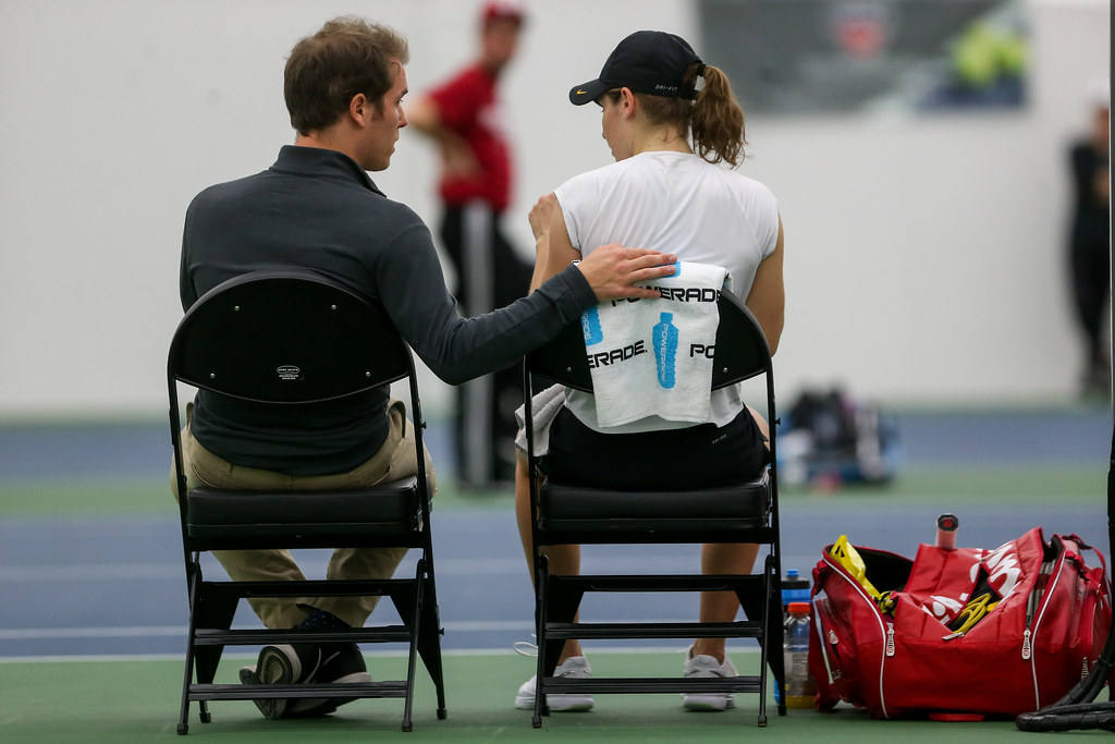 Iowa's assistant coach Drew Lied talks with Elise van Heuvelen between sets during her singles match against Indiana's Madison Appel.