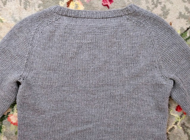 Grey handknit jumper.