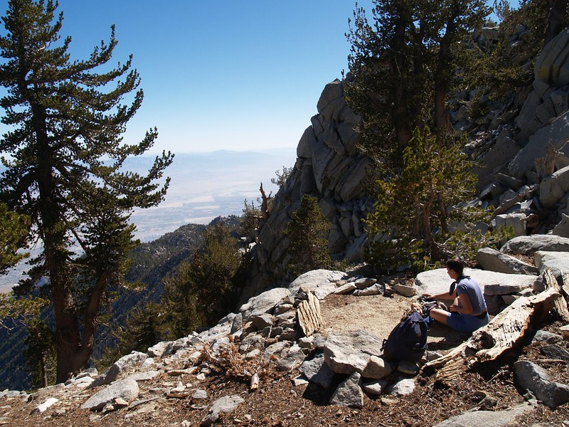 Vicki taking a break at the stealth camping spot at Miller Peak Saddle, with Palm Springs far below