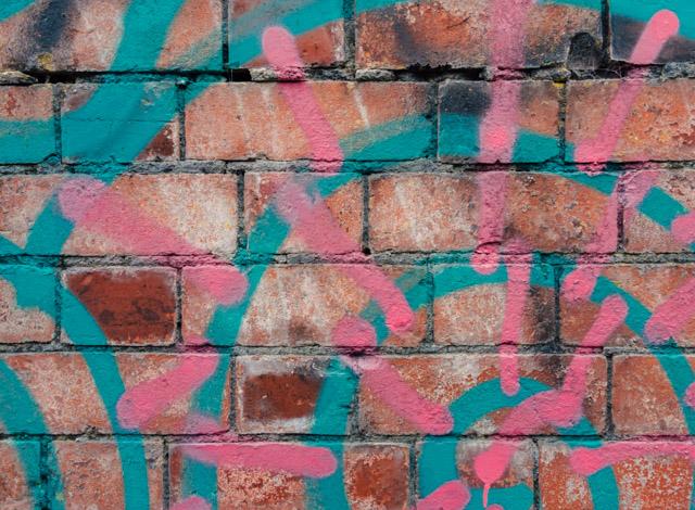 pink and blue graffiti on brick wall
