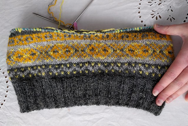 An image of a flat laid, partially knitted fair isle hat.