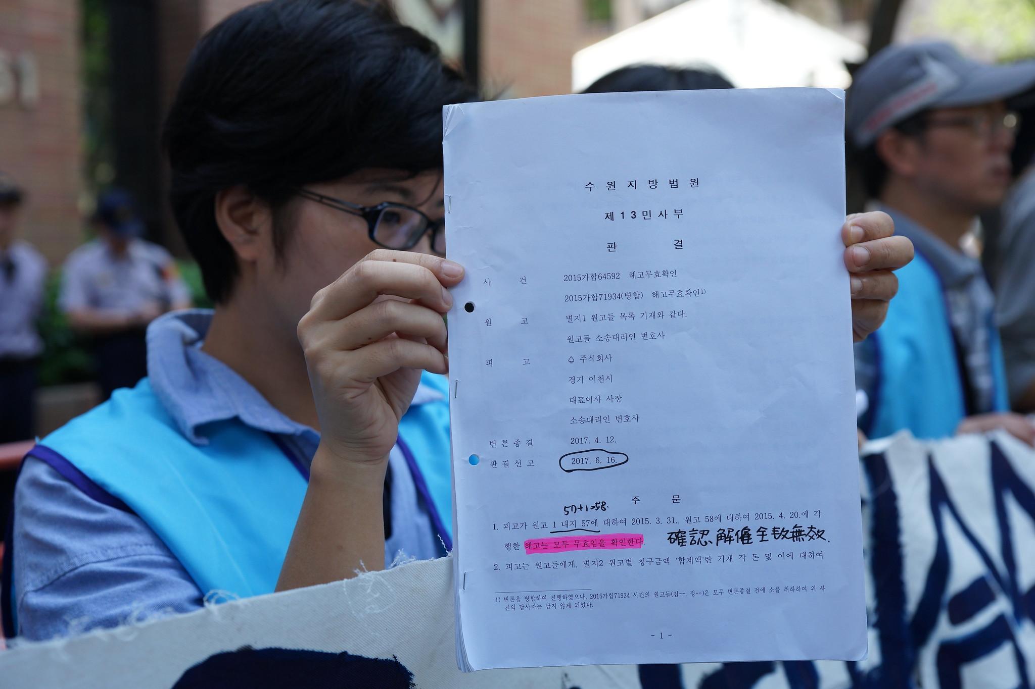 聲援勞團拿著韓法院的一審判決書,呼籲永豐餘撤回上訴。(攝影:王顥中)